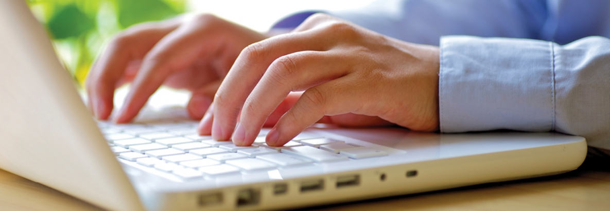 Hands typing on a laptop computer
