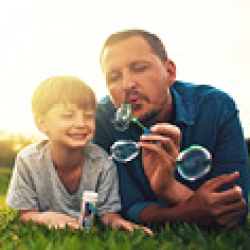 picture of a father and son blowing bubbles